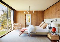 Wrapped in a Phillip Jeffries wall covering, the master bedroom features a bespoke headboard dressed in a Christopher Farr cloth fabric from Holland & Sherry   archdigest.com
