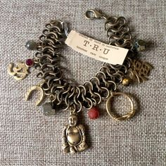 TRU Jewelry Buddha Charm Bracelet NWT This gorgeous bronze bracelet made by TRU Jewelry has an Asian and Bohemian vibe. Charms include Buddha, a Chinese kanji, a brass ring, a horseshoe and an Om symbol with a red crystal. Also had pyrite and labradorite accents. 7 1/2 inches in length. Never been worn, NWT. TRU Jewelry Jewelry Bracelets