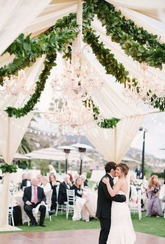 Stunning outdoor white tented wedding reception with hanging greenery decor; Featured Photographer: Michael Radford Photography
