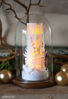 Craft this gorgeous DIY Paper Cut Winter Scene in a Glass Dome for your Christmas decorations this year! It's  easy and inexpensive to make!