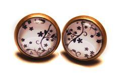 Dies sind kleine Ohrstecker mit einer Blumenranke vor weißem Hintergrund. Der Durchmesser des Bildchens beträgt 10mm. Verschlossen werden die Stecker