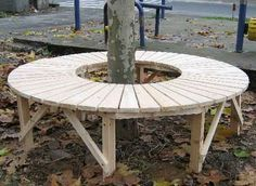 round gardens | Full circular tree bench with no back support in a public park.