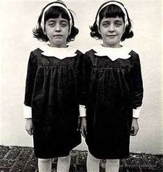 Diane Arbus Identical Twins, Roselle, N.J. 1967 — Young twin sisters Cathleen and Colleen Wade[26] stand side by side in dark dresses. The twin on the right slightly smiles and twin on the left slightly frowns.[28] This photograph is echoed in Stanley Kubrick's film The Shining, which features twins in an identical pose as ghosts