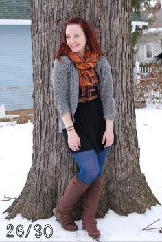 Black dress, brown boots, brown belt, grey open sweater cardigan, blue tights, orange scarf, green earrings