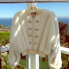 ST. JOHN FAUX FUR COAT Stunning St. John faux fur coat with decorative diamond buttons on front and cuffs. I wore it one time. In excellent condition, just needs to be dry cleaned. A bit of make up on the inside lining, otherwise is absolutely gorgeous. Size petite. St. John Jackets & Coats