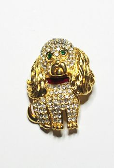 This adorable spaniel dog brooch was designed by Kenneth Jay Lane and is done in gold tone metal and clear crystals. In addition, there are green stones for the eyes and a bright red enamel collar. I think the design is so cute. If you love dogs, youll love this pin! The pin is 1-5/8 tall and 1-1/8 wide. It has all of its stones and is in Like New Condition. It is perfect for work , play or any special occasion. It would also make a great gift for someone. Dont miss the chance to get this…