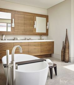In the master bathroom, a vein-cut travertine countertop complements custom eucalyptus cabinetry fabricated by Bayshore Tech. A sculptural tub from Wetstyle's Ove collection is fitted with a Graff floor-mounted tub filler. The Phoenix Day wall sconces are from Thomas Lavin.