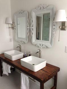 White bathroom with vessel sinks and wood table as vanity Like the table vanity