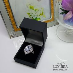 Placeholder, proposal or temporary engagement Ring.  Impressive large central stone surrounded by diamond simulants and set in 925 sterling silver.   Luxuria jewellery NZ