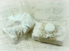 vintage match boxes - covered in vintage feed sack cloth or bleached muslin -  burlap wrapped around them - embellished with handmade fabric rosettes and vintage/antique lace. The white flower out of thin ripped fabric strips with rhinestone center is my favorite.  ♥♥♥
