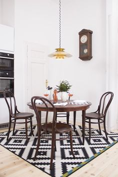 Some folks still feel like rugs under a dining table is a no-no, but choosing those that have a low pile and are easy to clean can look great in a dining room, helping set it apart from an open-plan great room and bring comfort to the space. Condo Living, Apartment Living, Living Spaces, Apartment Therapy, Bentwood Chairs, Room Decor, Wall Decor, Finding A House, Dining Room Furniture
