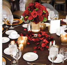 Rich red roses and dahlias mixed with greenery filled Venetian-style, frosted vases. Red petals and gold candleholders surrounded the base of the display. To add variety to the space, the florist created three different styles of centerpieces using the same flowers in different vases