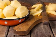 Raw potatoes in a vintage enamel bowl on old table Stock Photo