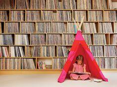 unhappyhipsters:  Boning up on indie rock history before her afternoon quiz. Oh, the perils of homeschooling. (Photo: Noah Webb; Dwell)