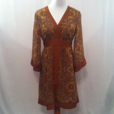 Paisley Print Boho Style Dress In excellent condition. Polyester. Machine wash cold. Bodice is lined. Back zipper. Ties in back. Browns and muted golds. Bust - 38 inches. Waist - 36 inches. Length - 37 inches. V-neck. New York & Company Dresses
