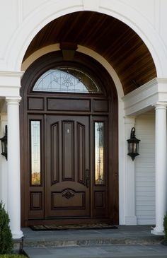 A beautiful wooden arch accentuates the curved window above the front entrance.
