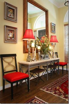 AFTER: Bright yellow paint fills the house. The moldings are painted white to highlight them. And red is introduced at the front door through the lampshades and chair fabric.