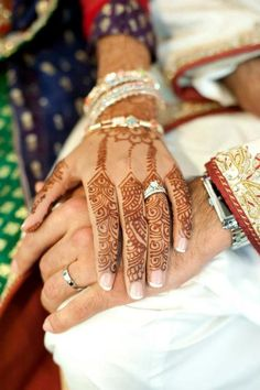 Henna Mehndi on a bride's hand as she holds the groom's