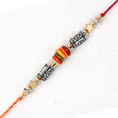 This is a dazzling Dori Rakhi that you can opt for your dear brother in India from Giftblooms.com. The center of the Rakhi comes with silver colored cylindrical metallic piece which as three flower designs. The two sides of the Rakhi are artistically decked with vibrant multicolored beads.