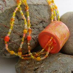 Now this is fun! This sunshine necklace consists of three strands of mixed glass seed beads attached to a beaded toggle with one of my unique polymer clay barrel beads as a focal/pendant. The beads are a mix of colours including shades of yellow, orange, vermillion and white. I used the same colours in the focal bead and the mokume gane technique to create a floral pattern. www.zibbet.com/fulgorine