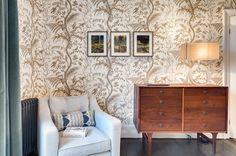 STILE BRITISH L'angolo lettura con una piccola poltrona affiancata alla cassettiera in legno antica. La zona notte è caratterizzata dalla carta da parati a tema floreale e dal parquet tinto scuro, a contrasto.