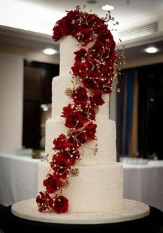 Gold Wedding Cakes Cascading flowers are a hot trend for 2013 © Claire Graham - Cake cutting is now a high point of your wedding reception, along with the speeches and the first dance. Click Cake talk about what's hot for 2013 Christmas Present Wedding Cake, Wedding Cake Red, Wedding Cake Fresh Flowers, Cool Wedding Cakes, Elegant Wedding Cakes, Beautiful Wedding Cakes, Wedding Cake Designs, Wedding Cake Toppers, Beautiful Cakes