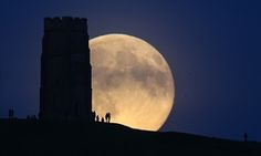 The moon rises over people gathered on Glastonbury Tor in Somerset, England.