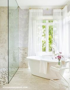 Contemporary bathroom features a freestanding tub placed and a lucite accent table catty corner in front of windows placed in front of windows dressed in white sheer curtains placed next to a seamless glass shower.
