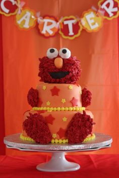 Two tiers of cake with a rice cereal Elmo. Elmo is covered with buttercream (took 2 1/2 jars of food dye to get him red!!!!). Customer Nico...