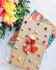 Geschenkverpackungen basteln mit Pompoms und Bänder bemusterte und nicht bemusterte Geschenkpapier auf zwei Geschenke