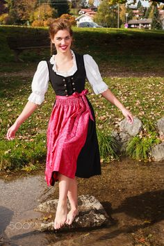 Happy beautiful woman in a dirndl - Happy beautiful woman in a dirndl playing barefoot in a stream in a park balancing on a rock smiling at the camera