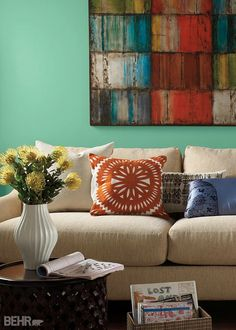 Bring Tropical Trail color to your family room to add a hint of tranquility to a chaotic environment. This serene teal blue BEHR paint color pairs well with bold colors and patterns, like in this abstract painting and in the throw pillows.