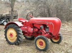 tractor pulling leaves to the edge of the property and riding on the back or steering with him.