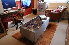 A very unusual Pinball Machine Coffee Table. This is constructed from an early 1990's Street Fighter pinball machine playing field. All electrical components have been removed, incorporated into a brushed stainless steel surround, fitted with adjustable feet and topped-off with tough 6mm safety glass. The lights are powered by low voltage lamps under the playing field gels which result is a very eye-catching and unusual and fun table. This weighs about 40kg and the dimensions are approx…