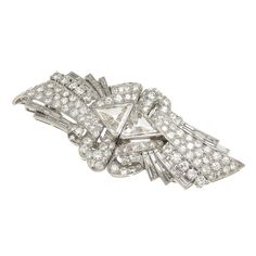 1930s Diamond Platinum Dress Clips. Circa 1930s Art Deco Platinum and Diamond Dress Clips that fasten together so as to be also worn as a single Brooch. Set with round and Baguette Diamonds totaling 3.25 carats and centrally set with stepped cut Triangle shaped Diamonds totaling 1.50 carats, for a total Diamond weight of 4.75 carats, 2 3/8 inch in length.