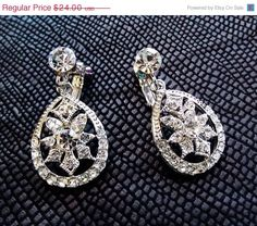 This sparkly design features an elegant filigree set with clear Swarovski crystals. These are clip-on earrings with hinged backs that have screws to