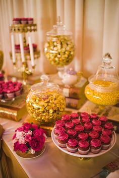 Beauty and the Beast candy table: gold candy, candelabra, mini rose cupcakes, fresh spray roses, and Mrs Potts and Chip