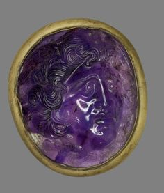 Amethyst cameo engraved with a head of Medusa in high relief, with wings above her temples and serpents coiled in her hair and meeting under her chin.