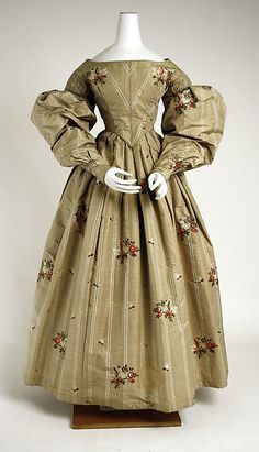 Dress 1836, British, Made of silk.  Taupe silk with lighter beige striping, and exquisitely embroidered with floral sprigs.  Classic elements of gowns of this period:  boat neckline, massive puffed sleeves attach to the bodice from drop shoulders, cinched waist and full gathered skirt.