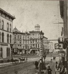 """Photo taken circa 1880–81 from second story window of William T. Powers Metropolitan Hall east of """"Kent"""" Alley from Powers Opera House. The Col. Edwin Sheldon (E. S.) Pierce Clothing Tower Block with Clock built in 1875-76 Pearl Street and Monroe/Canal Avenues. One of the first electric street lights dons the entrance to Powers Opera House."""