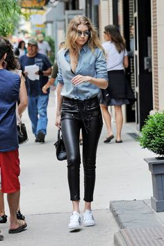GIGI HADID in New York wearing a denim button-down shirt with lace-up leather pants by Unravel, plus Adidas sneakers.