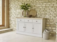 The Corndell Annecy large sideboard creates loads of storage in a hallway or dining room whilst looking stunning. The cool hand painted Cotton finish (1 of 7 colour options) looks crisp against the limed oak top and mellow Cotswold stone walls. Country chic styling available in the UK finest furniture stores.