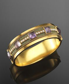 Yellow Gold Cabochon Amethyst, Pearl and Enamel Hinged Bangle Bracelet, Carlo Giuliano, c 1890.  A yellow gold hinged bangle is studded with sugarloaf cabochon amethysts, spaced between rows of pearls and green enamel oval motifs.