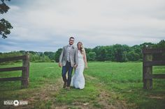 Connecticut wedding photographer zukas hilltop barn bride and groom walking field and wooden fence www.devolveimaging.com