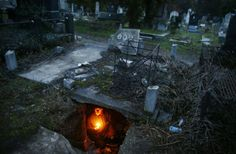 Bratislav Stojanovic, a homeless man, hold candles as he sits in a tomb where he lives in southern Serbian town of Nis