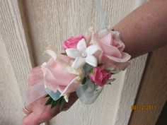 Wrist corsage with blush roses, hot pink spray roses and white stephanotis.