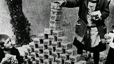 German children playing with Reichsmarks during the heavy inflation of the 20s. The German currency had become so worthless it was reduced to children's toy bricks.