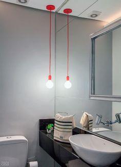No banheiro das visitas, é o vermelho do pendente que se destaca do cinza das paredes. Há ainda outro elemento surpresa: uma moldura antiga, pintada com spray prateado, presa no espelho com fita banana. Lustre: soma pendente (R$ 70) e lâmpada do tipo bolinha (R$ 20).