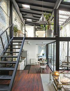 sol en parquet foncé en bois, salon moderne avec plantes vertes, lustre en fer suspendu
