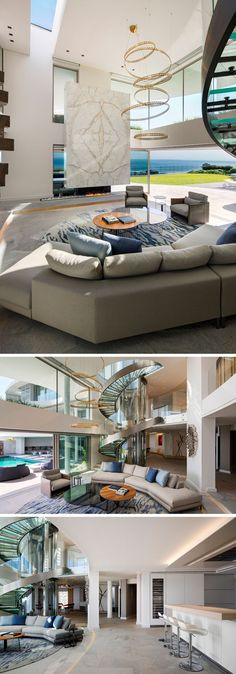 Inside this modern house, there's a living room with a double height ceiling. Throughout the interior, white marble, granite, brushed stainless steel and bronze elements have been included to contrast the white walls that are ever present throughout the house. #LivingRoom #ModernLivingRoom #InteriorDesign #SpiralStaircase